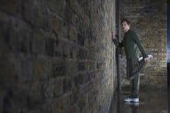Uomo che allunga gamba contro il muro di mattoni Immagini Stock