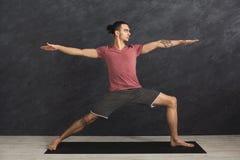 Uomo che allunga le mani e le gambe alla palestra Fotografie Stock