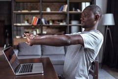 Uomo che allunga le mani mentre lavorando Immagini Stock