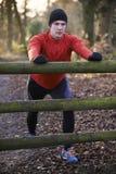 Uomo che allunga sul terreno boscoso passato di inverno Immagine Stock Libera da Diritti