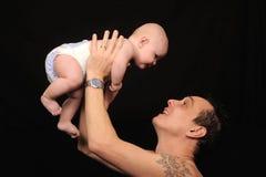 Uomo che alza allegro figlio   Fotografie Stock Libere da Diritti