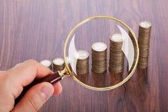 Uomo che analizza le pile della moneta con la lente d'ingrandimento Fotografia Stock