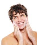 Uomo che applica crema d'idratazione dopo la rasatura Fotografia Stock
