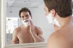 Uomo che applica crema da barba Fotografie Stock