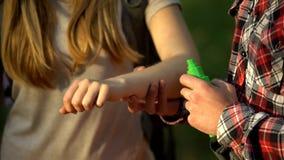 Uomo che applica crema di raffreddamento sul braccio delle signore dopo il morso di zanzare, cosa repellente di insetto fotografie stock