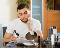 Uomo che applica crema facciale a casa Fotografia Stock