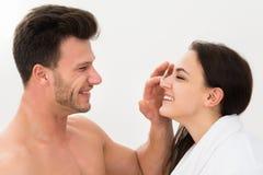Uomo che applica idratante sul naso della donna Immagini Stock Libere da Diritti