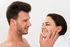 Uomo che applica idratante sulla guancia della donna Fotografia Stock