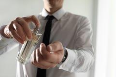 Uomo che applica profumo sul polso all'interno fotografie stock libere da diritti