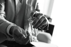 Uomo che applica profumo sul polso all'interno, primo piano Effetto in bianco e nero fotografia stock