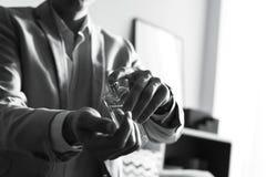 Uomo che applica profumo sul polso all'interno, primo piano Effetto in bianco e nero fotografia stock libera da diritti