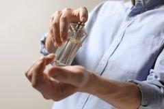Uomo che applica profumo sul polso contro il fondo leggero immagini stock