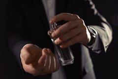 Uomo che applica profumo sul polso contro il fondo nero fotografia stock libera da diritti