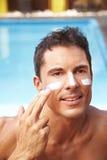 Uomo che applica protezione solare al suo fronte Immagini Stock