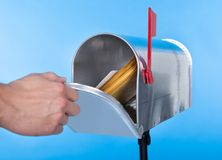 Uomo che apre la sua cassetta delle lettere per rimuovere posta Immagini Stock Libere da Diritti