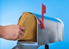 Uomo che apre la sua cassetta delle lettere per rimuovere posta Fotografia Stock Libera da Diritti