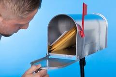 Uomo che apre la sua cassetta delle lettere per rimuovere posta Immagini Stock