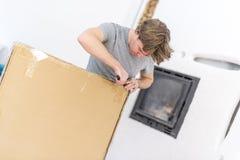 Uomo che apre tagliando una grande scatola Fotografie Stock