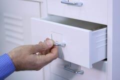 Uomo che apre un cassetto in un gabinetto Fotografia Stock Libera da Diritti