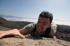 Uomo che arrampica una montagna Fotografia Stock