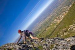 Uomo che arrampica una montagna Immagine Stock