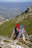 Uomo che arrampica una montagna Fotografie Stock Libere da Diritti