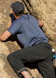 Uomo che arrampica una roccia Immagini Stock Libere da Diritti