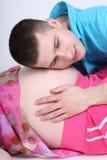 Uomo che ascolta la pancia della sua moglie incinta fotografie stock libere da diritti