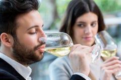 Uomo che assaggia vino bianco in ristorante Fotografia Stock Libera da Diritti