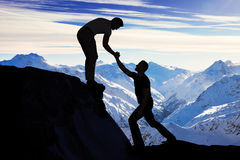 Uomo che assiste amico maschio in roccia rampicante fotografie stock