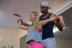 Uomo che assiste ballerino femminile nell'allungamento Fotografie Stock Libere da Diritti