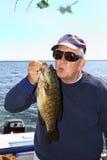 Uomo che bacia un pesce - spigola di Smallmouth di Ontario di lago fotografie stock