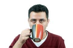 Uomo che beve da una tazza immagini stock