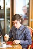 Uomo che beve grande latte ad una tavola del caffè immagini stock libere da diritti