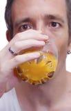 Uomo che beve il succo di arancia Fotografie Stock Libere da Diritti