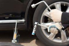 Uomo che cambia la gomma sul suo veicolo Fotografie Stock Libere da Diritti