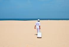 Uomo che cammina ad un deserto con bagagli Immagini Stock Libere da Diritti