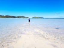 Uomo che cammina in chiara acqua blu immagine stock libera da diritti