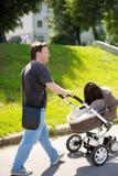 Uomo che cammina con il passeggiatore di bambino Fotografie Stock