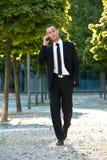 Uomo che cammina con il telefono Immagine Stock