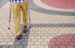 Uomo che cammina con le grucce Immagini Stock