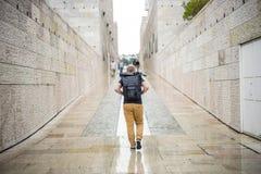 Uomo che cammina con lo zaino con il treppiede durante il tempo piovoso immagine stock
