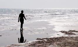 Uomo che cammina da solo nella spiaggia Fotografie Stock