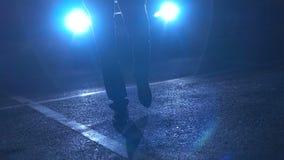 Uomo che cammina davanti ai fari dell'automobile stock footage