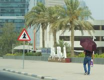 Uomo che cammina davanti alla banca Qatar di Doha fotografia stock libera da diritti