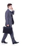 Uomo che cammina e che comunica sul telefono Immagine Stock