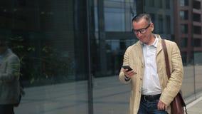 Uomo che cammina e che per mezzo dello smartphone stock footage