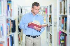Uomo che cammina in libro di lettura delle biblioteche Fotografia Stock Libera da Diritti