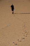 Uomo che cammina nel deserto immagine stock