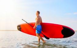 Uomo che cammina nell'acqua con il bordo del SUP immagini stock